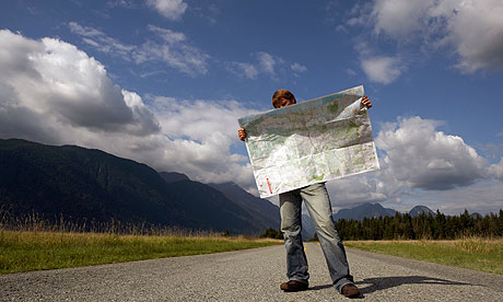 A man standing at the side of a rural road, looking at an unfolded road map.