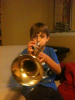 A beginning trumpet student, playing some notes on his trumpet.