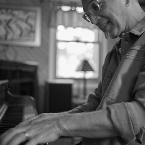 Earl MacDonald playing the piano at home.